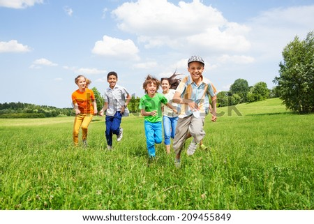 Positive kids play and run together in the field - stock photo