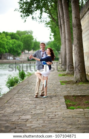 Positive laughing couple is dancing on the Seine embankment in Paris - stock photo