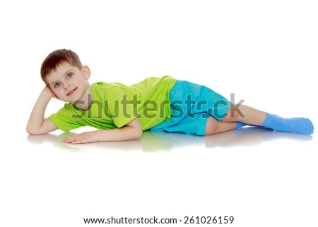 positive little boy lying on the floor - isolated on white.