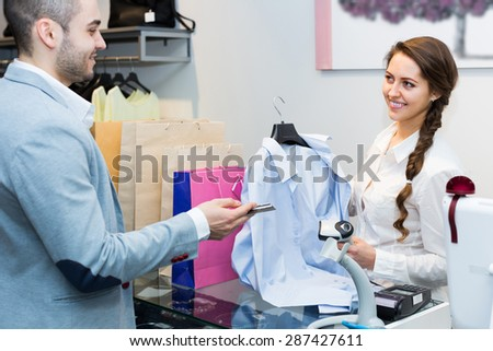 Positive male client paying by card for new clothes at store counter - stock photo