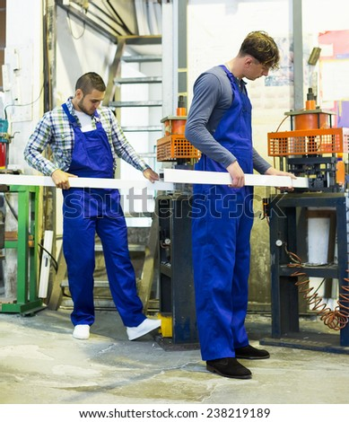 Positive males working together on a machine indoor - stock photo