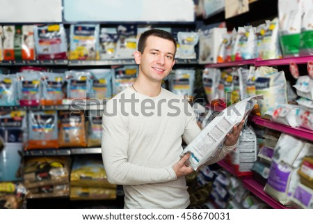 Positive man watching diet products and smiling in pet store