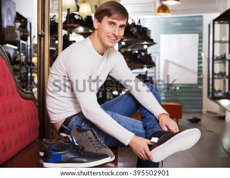 Positive man with the shoe in his hands - stock photo