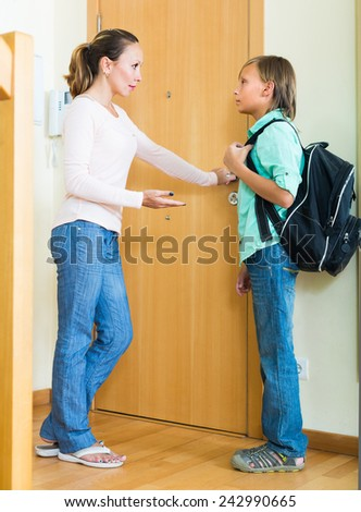 Positive mature woman lecturing boy before he goes to school  - stock photo
