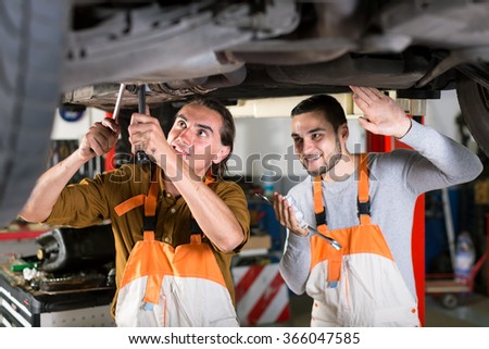 Positive mechanics in white and orange coveralls at automotive service station are repairing exhaust system of a lifted up car - stock photo