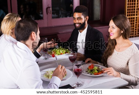 positive middle class american people enjoying food in cafe and talking - stock photo