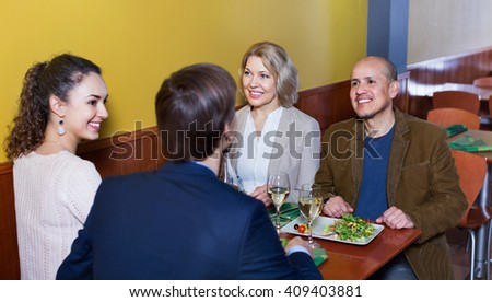 Positive middle class people enjoying food and wine in cafe - stock photo
