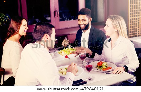 positive middle class people enjoying food in cafe and talking