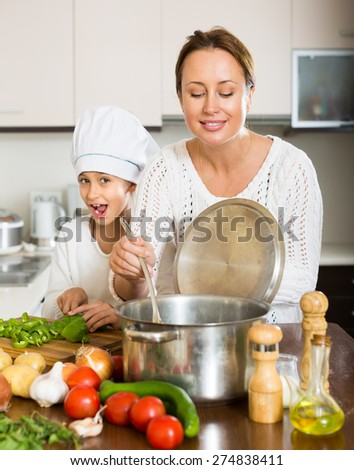 Positive mother and her cheerful daughter preparing soup together. Focus on woman - stock photo