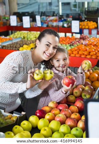 Positive mother and  little daughter choosing seasonal fruits in grocery