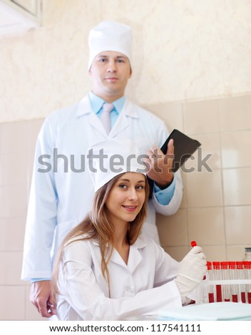 Positive nurse and male doctor with test tubes in clinic lab