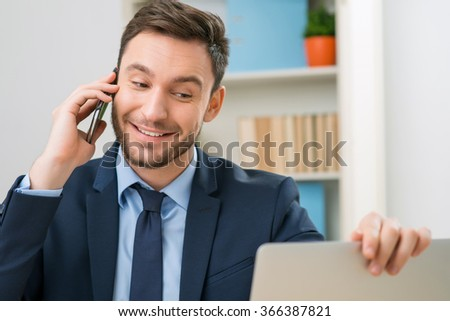 Positive office worker talking on mobile phone