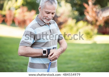 Positive old man fixing his sport glove