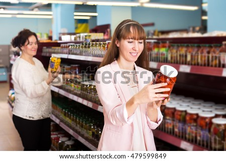 Positive ordinary women purchasing pickled vegetables at East-European supermarket