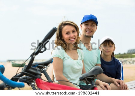 Positive parents and boy with bicycles at seashore