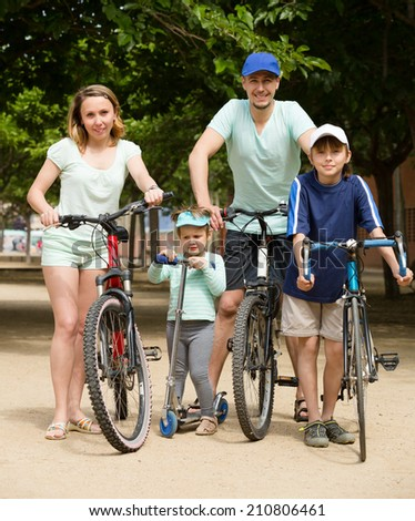 Positive parents and kids traveling through city by bicycles