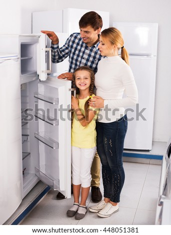 Positive parents with daughter choosing refrigerator in home appliance store