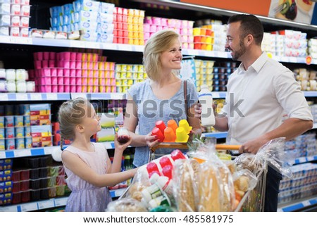 Positive parents with daughter holding yogurt from refrigerator in hypermarket
