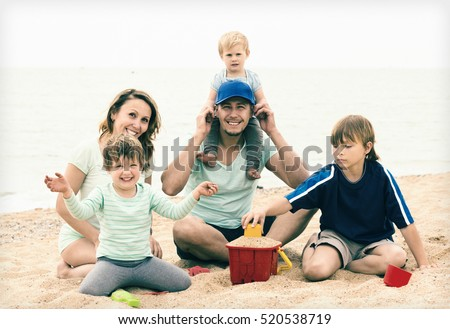 Positive parents with kids on vacation sitting at sandy beach
