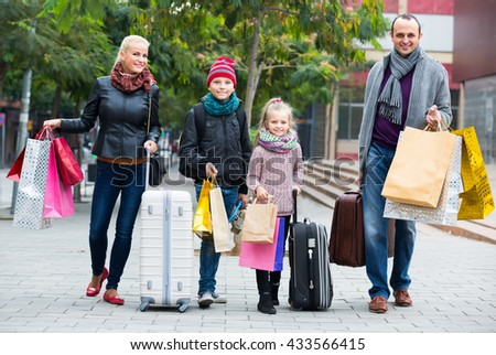 Positive parents with school age children enjoying shopping tour
