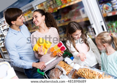 Positive parents with two daughters buying fruit yoghurt and pudding