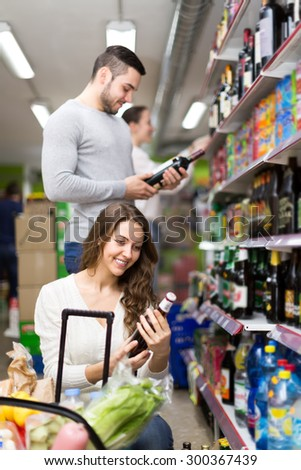 Positive people buying beverages for dinner at food shop - stock photo