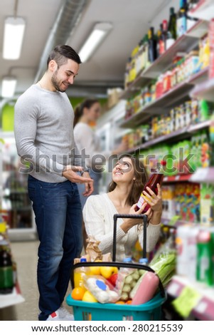 Positive people selecting juice and soda at grocery. Focus on the woman - stock photo