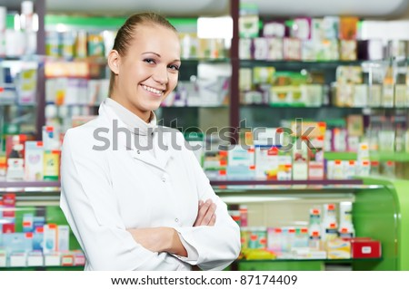 positive pharmacist chemist woman standing in pharmacy drugstore - stock photo