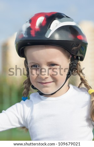 positive portrait of young little skater girl outside in protective helmet