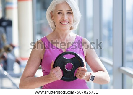 positive pretty senior lady exercising in a gym.