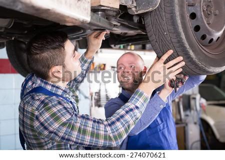 Positive  professional mechanics fixing car tire leak  - stock photo