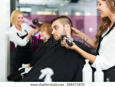Positive professional woman hairdresser doing hairstyle for young men - stock photo