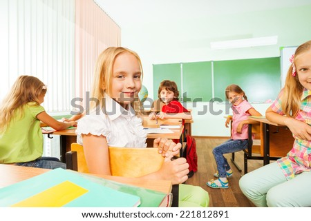 Positive pupils turned back of the class sitting