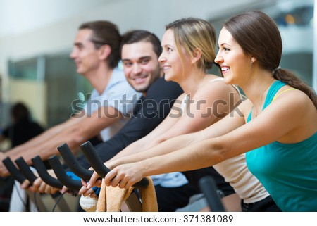 positive russian adults riding stationary bicycles in fitness club
