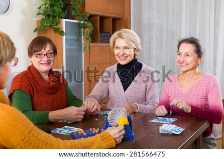 Positive russian senior female friends sitting at desk with lotto - stock photo
