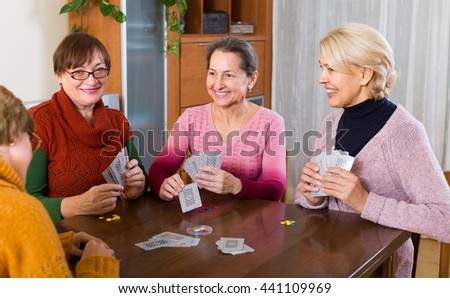 Positive russian senior female friends staking money during bridge - stock photo