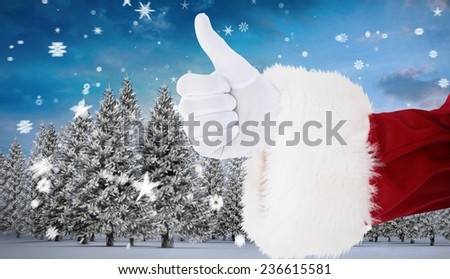 Positive santa claus with thumbs up against snowy landscape with fir trees - stock photo