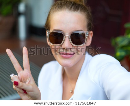 Positive selfie portrait of positive blonde girl wearing white jacket and sunglasses.Taking picture. Smiling cheerful blond-haired woman doing selfie - stock photo