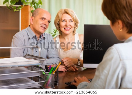 Positive senior couple opening saving account in bank - stock photo
