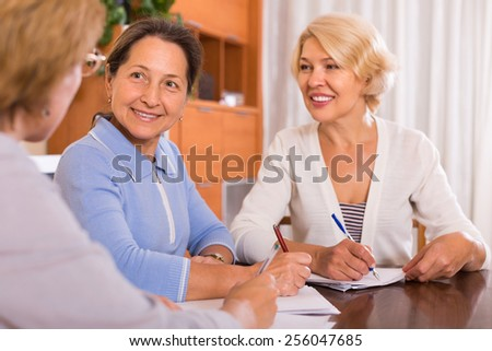 Positive senior ladies signing documents at notary. Focus on brunette - stock photo