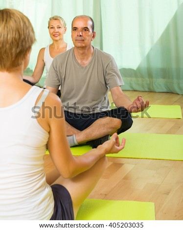 Positive senior mature couple practicing yoga with female instructor