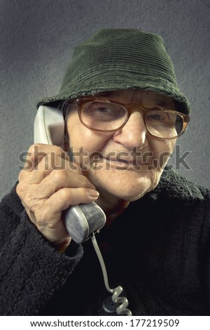 Positive senior woman talking on the phone on a vintage background. - stock photo