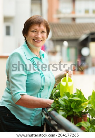 Positive senior woman watering decorative plants on balcony - stock photo