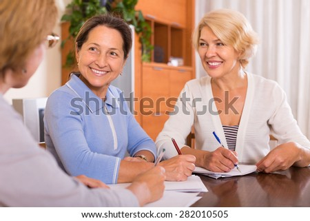 Positive senior women signing documents at notary. Focus on brunette
