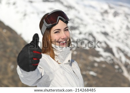 Positive skier woman gesturing thumb up in winter with a snowy mountain in the background               - stock photo