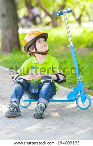 Positive small boy sits on scooter and looks up on path in city park - stock photo