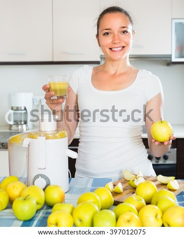 Positive smiling adult girl making juice from apples at kitchen