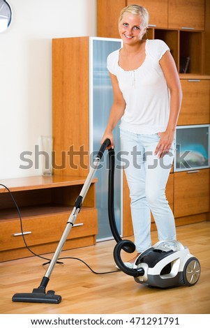 Positive smiling blonde girl in jeans vacuuming floor at home
