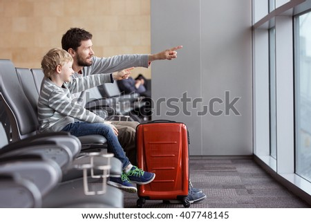 positive smiling boy and his father waiting at the airport for plane departure and pointing with fingers at something, vacation and travel concept - stock photo