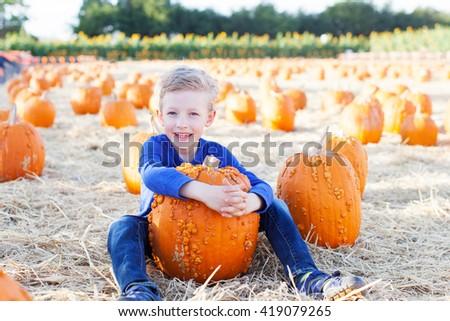 positive smiling boy holding pumpkin and enjoying pumpkin patch - stock photo